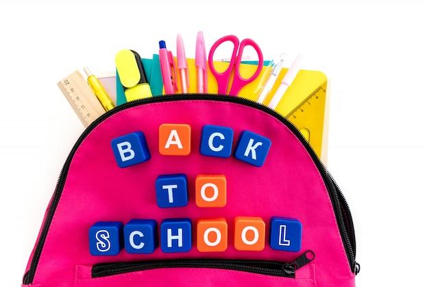 Torna al concetto di scuola. zaino con materiale scolastico su bianco.