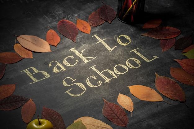 Torna al concetto di scuola. cornice di foglie d'autunno. gesso scritto a mano sulla lavagna