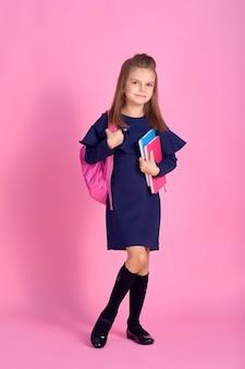 Torna al concetto di scuola la metà girato foto ritratto di bella ragazza intelligente bella fiduciosa con il taccuino del quaderno che indossa lo zaino luminoso rosa del vestito dell'uniforme scolastica isolato