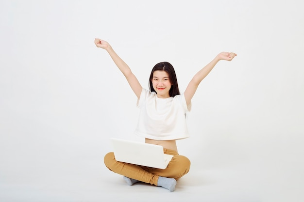 Torna al concetto di scuola, felice giovane donna asiatica bella seduta attraente sul pavimento con le gambe incrociate e utilizzando il computer portatile