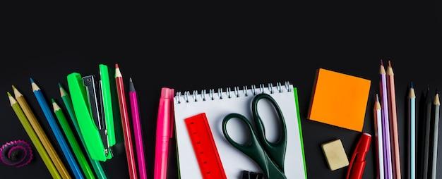 Torna al concetto di scuola. forniture per ufficio su uno sfondo di lavagna. posto per il testo. formato banner