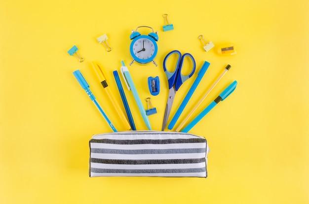 Torna al concetto di scuola. astuccio con cancelleria scolastica su sfondo giallo. carta per notebook, matita, graffetta e nota adesiva con spazio per le copie,