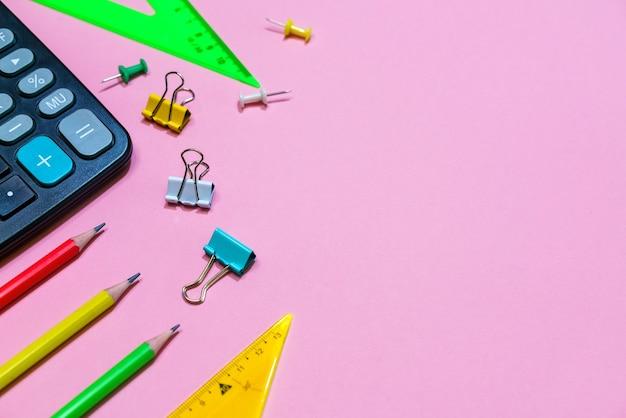 Torna al concetto di scuola scuola e forniture per ufficio su uno sfondo rosa copia spazio calcolatrice e bri...