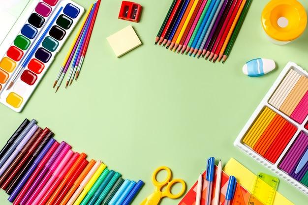 Torna al concetto di scuola. materiale scolastico su uno sfondo pastello