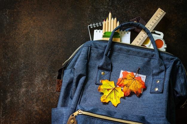 Torna al concetto di scuola materiale scolastico con zaino blu sul tavolo vista dall'alto