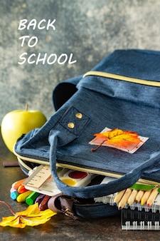 Torna al concetto di scuola forniture scolastiche con zaino blu sul tavolo