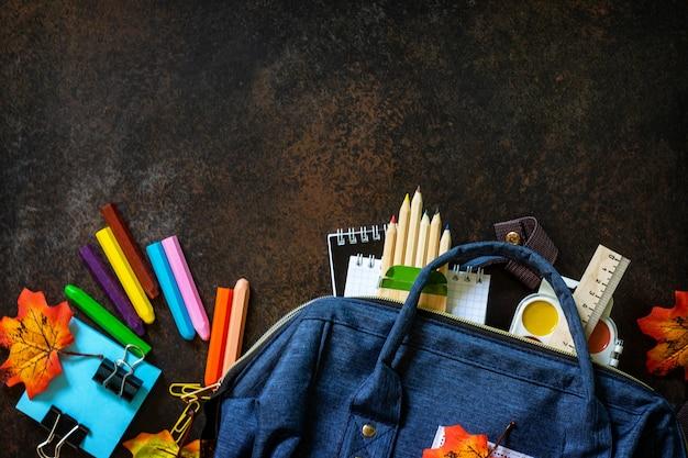Torna al concetto di scuola materiale scolastico con zaino blu vista dall'alto