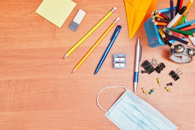 Torna al concetto di scuola, cancelleria sulla scrivania e maschera medica, università, college, lay flat, copia spazio