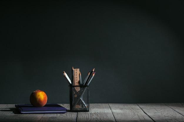 Torna al concetto di scuola. cancelleria con frutta sul tavolo