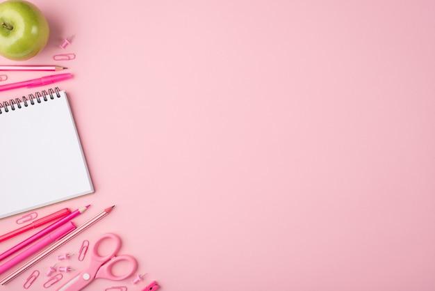 Torna al concetto di scuola. in alto sopra la composizione fotografica vista dall'alto di mela e cancelleria colorata isolata su sfondo rosa pastello con copyspace