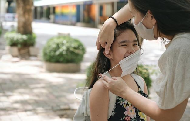 Torna al concetto di scuola con mamma asiatica che indossa la maschera per il viso per il suo bambino