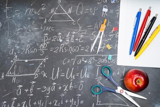Concetto di ritorno a scuola con materiale scolastico colorato e mela sulla lavagna, sfondo vista dall'alto con formule matematiche