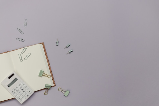Torna al concetto creativo di scuola. studio o ufficio con cancelleria come taccuino, calcolatrice e clip su uno sfondo di carta viola. piatto minimalista, vista dall'alto con spazio di copia.