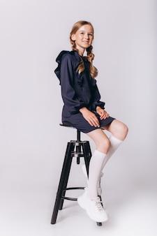 Di nuovo a scuola. carina adorabile ragazza bionda caucasica in uniforme scolastica su sfondo bianco