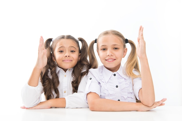 Di nuovo a scuola. scolari svegli che sostengono le mani isolate su bianco. piccole studentesse che hanno lezione nella scuola primaria. adorabili bambine che si divertono a scuola.