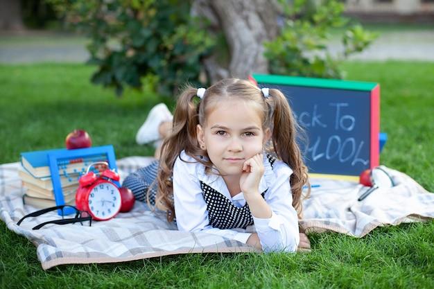 Di nuovo a scuola. studentessa sorridente sveglia che si siede sull'erba con pranzo, libri vicino alla scuola