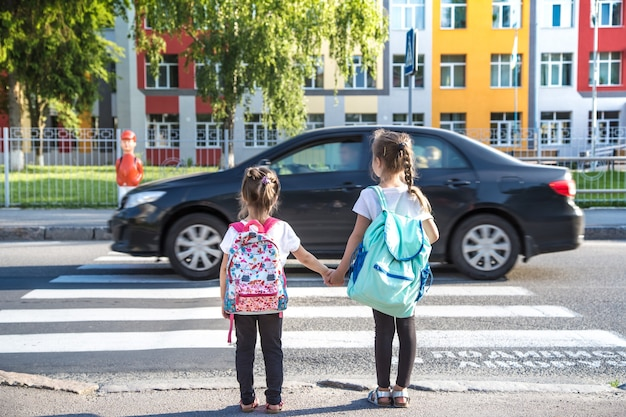 Torna al concetto di educazione scolastica con ragazzine, studenti elementari, portando zaini che vanno a lezione