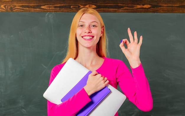 Di nuovo a scuola. formazione scolastica. l'insegnante femminile sorridente nell'aula mostra il segno ok. università. università.