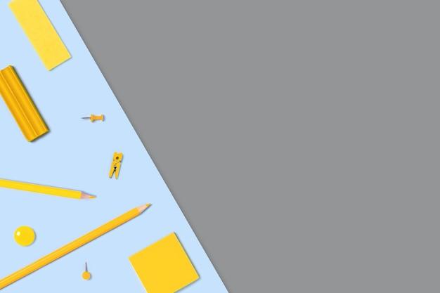 Ritorno a scuola sdraiato con materiali per scrivere su sfondo giallo e grigio