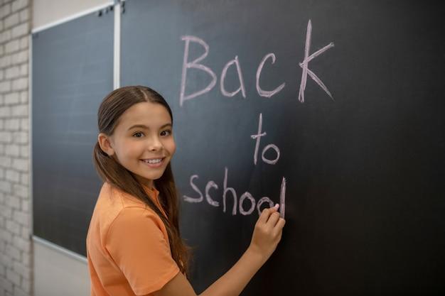 Di nuovo a scuola. una ragazza in maglietta arancione scrivendo sulla lavagna