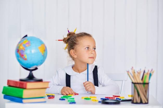 Di nuovo a scuola. allievo sorridente felice alla scrivania. bambino in classe con matite, libri. ragazza del bambino della scuola primaria. primo giorno d'autunno.