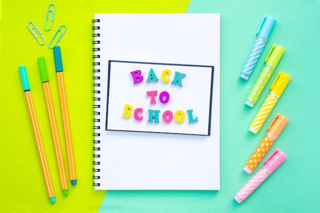 Iscrizione di ritorno a scuola fatta di lettere multicolori una pila di quaderni su una sovrapposizione a spirale