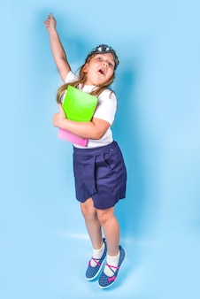 Ritorno a scuola, ispirazione per l'apprendimento dei bambini nell'educazione scientifica, ricerca della conoscenza. carina studentessa delle elementari in uniforme blu bianca, con occhiali volanti, che salta su uno sfondo blu colorato