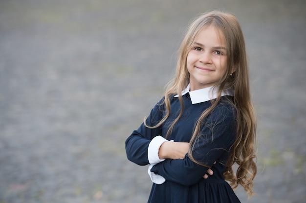 Ritorno a scuola e aspetto figo. bambino felice di tornare a scuola. piccola ragazza indossa l'uniforme scolastica. codice di abbigliamento. educazione formale. avviare. 1 settembre. torna a scuola con stile, copia spazio.