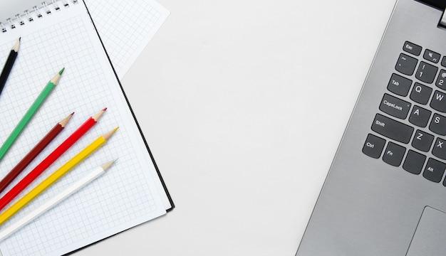 Torna al concetto minimalista di scuola. computer portatile, matite colorate, taccuino su bianco