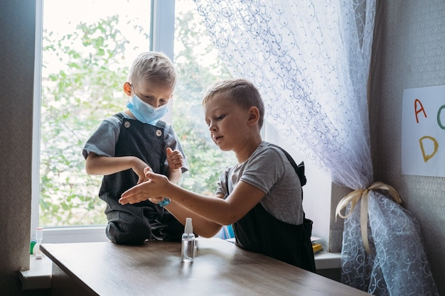 Ritorno a scuola di sicurezza scolari che indossano maschere e usano antisettico in classe a scuola bambini