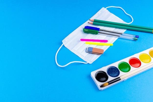Di nuovo a scuola. accessori per la scuola su sfondo blu. banner fotografico, vista dall'alto, spazio per il testo.