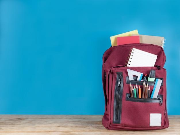 Di nuovo a scuola . borsa di scuola e forniture su blu
