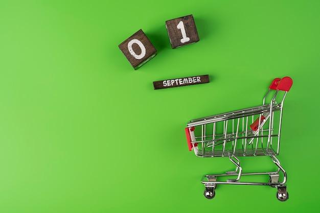 Torna al concetto di shopping scolastico su uno sfondo verde data di calendario 1 settembre con spazio di copia