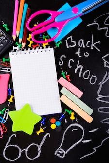 Torna a scuola stazioni con taccuino vuoto con spazio copia sul tavolo nero con messaggio in gesso