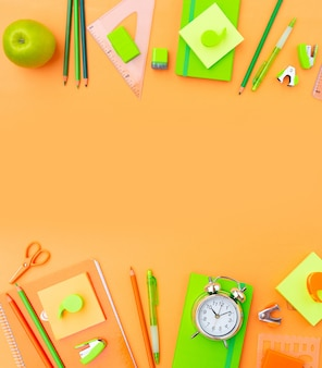 Scena piatta in stile ritorno a scuola con materiale scolastico arancione e verde su sfondo arancione chiaro