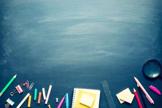 Torna a materiale scolastico e accessori per ufficio su sfondo lavagna. vista dall'alto design