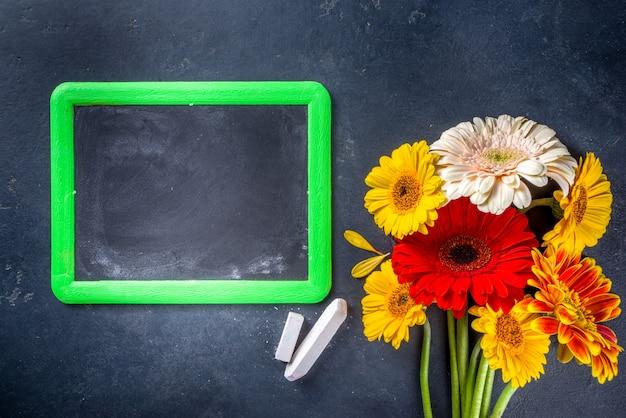 Di nuovo a scuola. festa degli insegnanti . bouquet di fiori di gerbera con gesso su lavagna nera