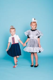 Di nuovo a scuola. due studentesse su sfondo blu. ragazza studentessa e la sua sorellina in studio in abiti scolastici.