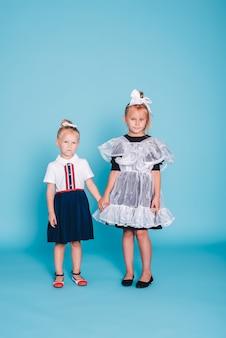 Di nuovo a scuola. due studentesse su sfondo blu. ragazza studentessa e la sua sorellina