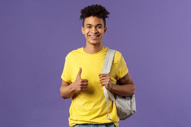 Ritorno a scuola, concetto universitario. il ritratto dello studente maschio bello allegro descrive le sue vacanze estive ai compagni di classe, mostra la raccomandazione, l'approvazione del pollice in su, tiene lo zaino