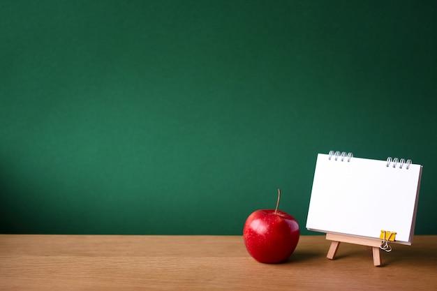 Ritorno a scuola con il taccuino aperto su cavalletto in miniatura e mela rossa su superficie di legno