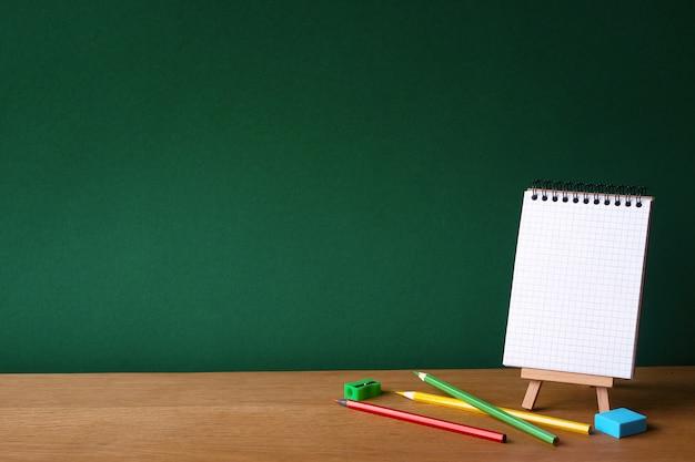 Ritorno a scuola con il taccuino aperto su cavalletto in miniatura e diverse matite colorate su superficie di legno sullo sfondo di un bordo di gesso verde pulito