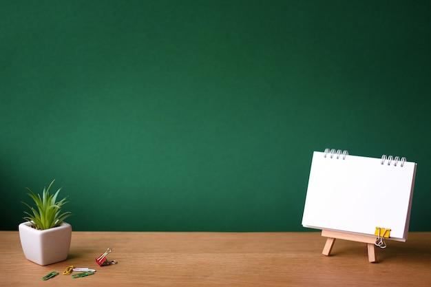 Ritorno a scuola con quaderno aperto su cavalletto in miniatura e piccola succulenta in una pentola bianca su superficie di legno sullo sfondo di una lavagna pulita verde