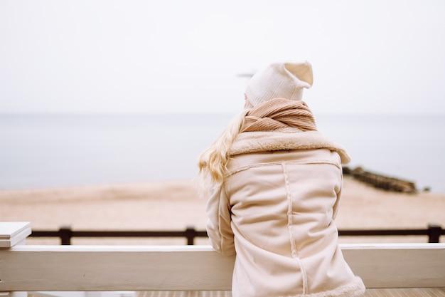 Colpo posteriore della donna dai capelli bionda gode di vista sul mare al giorno d'inverno. la donna indossa una giacca leggera, un cappello, una sciarpa e una bevanda calda.