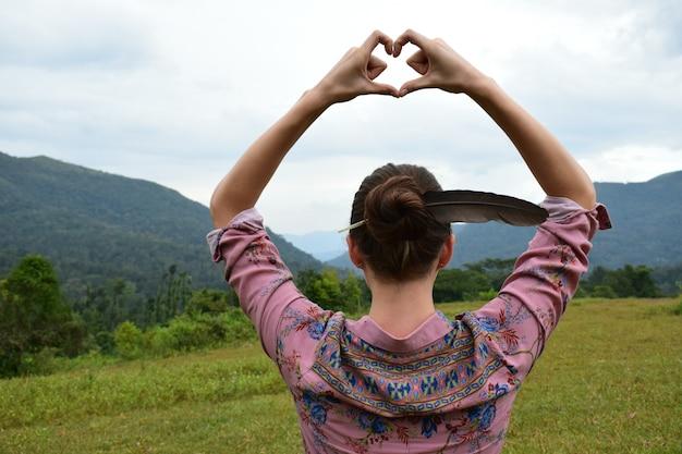 Colpo posteriore di una ragazza con una piuma tra i capelli che mostra il cuore con le mani