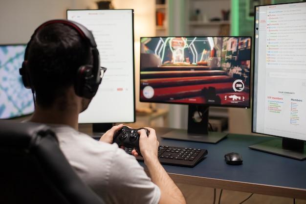 Colpo posteriore di giovani che giocano a videogiochi sparatutto online sul computer utilizzando un controller wireless.