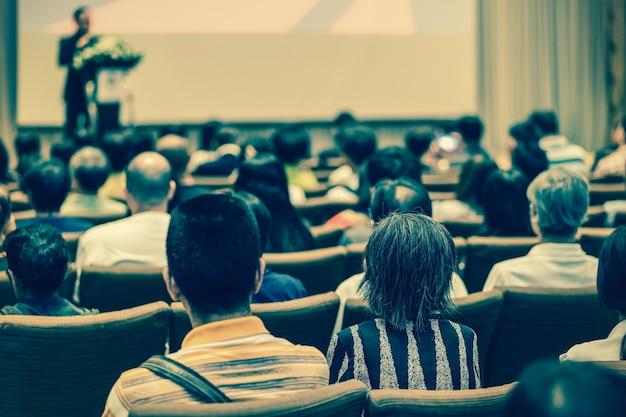 Lato posteriore del pubblico che ascolta lo speaker con il podio sul palco nella sala della conferenza