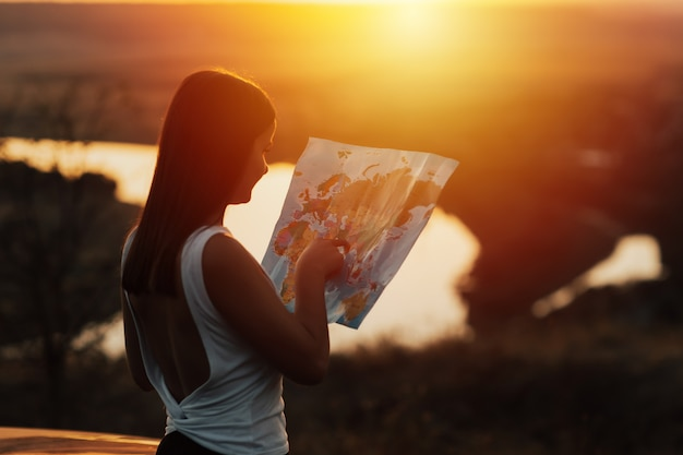 Lato posteriore della ragazza del viaggiatore che cerca la giusta direzione sulla mappa