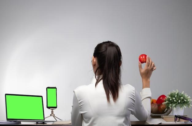 Vista laterale posteriore della donna dell'ufficio che lavora duro in ufficio con il taccuino del dispositivo dello schermo verde, che tiene la frutta della mela rossa