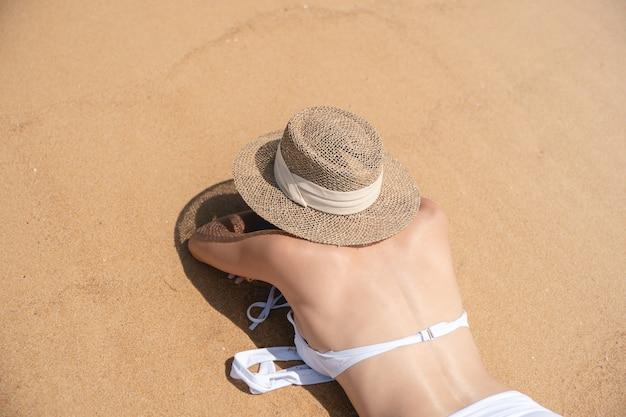 Lato posteriore della donna in bikini sdraiato sulla spiaggia di sabbia rilassante per prendere il sole.